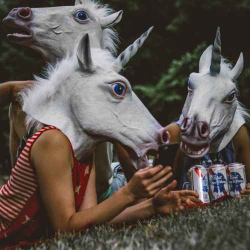three persons wearing unicorn costumes